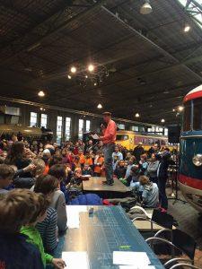 Ton Mackaaij spreekt de menigte kinderen toe tijdens het toernooi van 2016 in het Spoorwegmuseum.